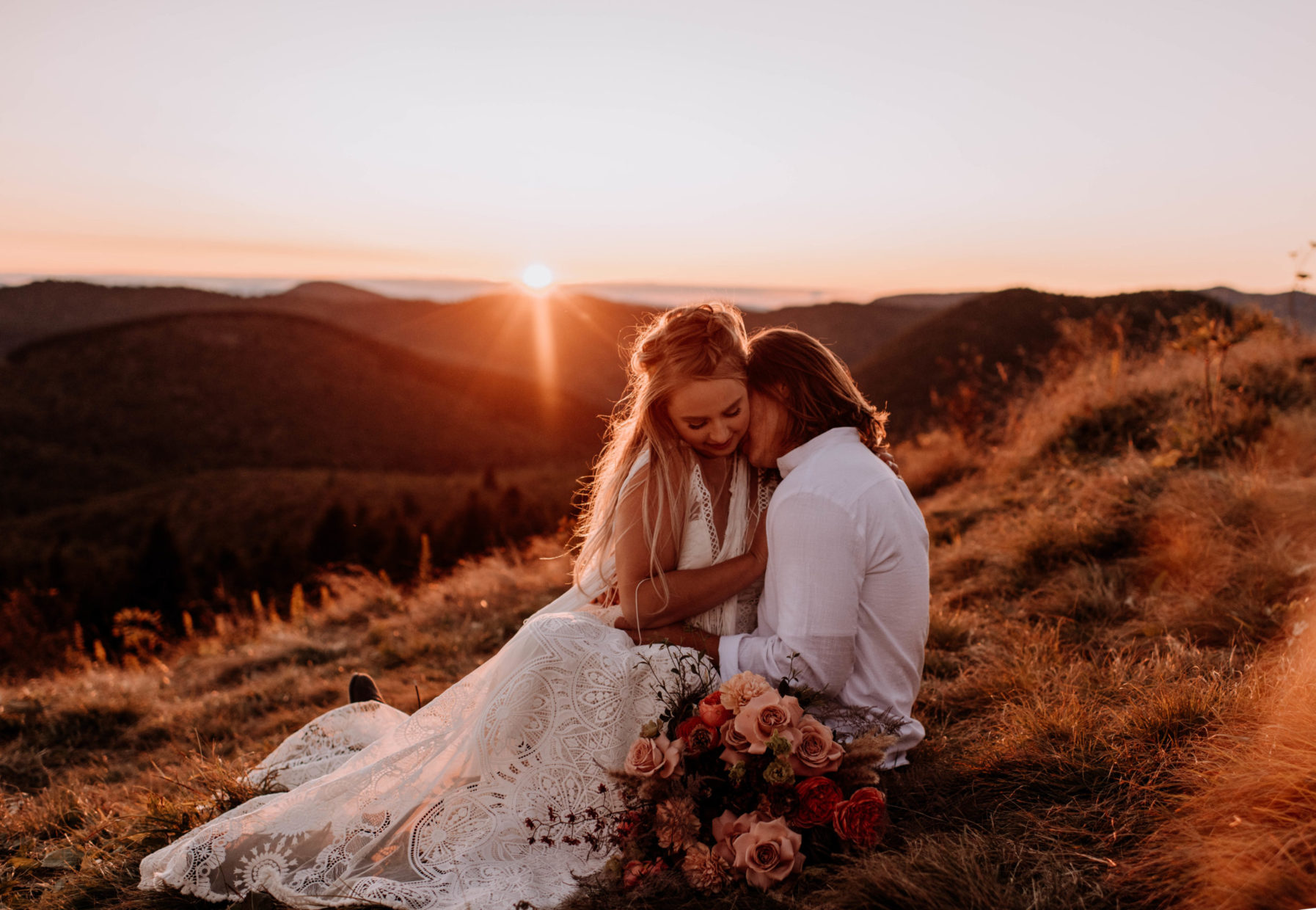 bride and groom sitting next to bouquet of flowers