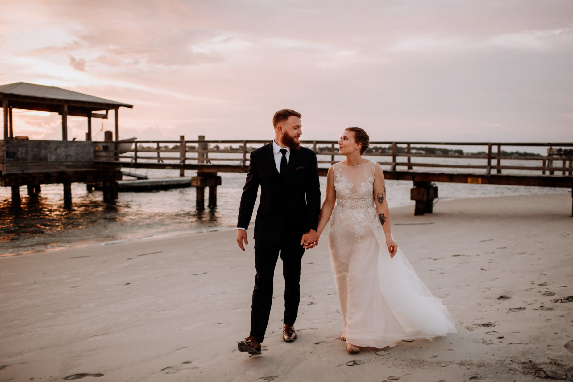 bride and groom walking along beach at sunset